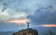 站在岩石上张开双臂的人