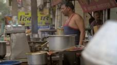 男人在货摊上给食物加香料。